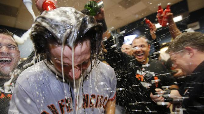 San Francisco Giants starting pitcher Madison Bumgarner, left, is showered by teammates as they celebrate after Bumgarner threw a four-hitter against the Pittsburgh Pirates in the National League wild-card baseball playoff game in Pittsburgh on Wednesday, Oct. 1, 2014. The Giants won 8-0. (AP Photo/Gene J. Puskar)