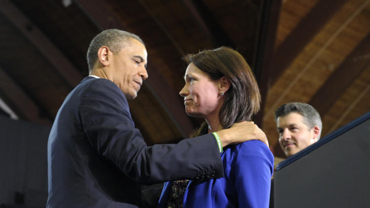 President Barack Obama looks at Nicole Hocklys and her husband Ian, right, after she introduced him at the University of Hartford in Hartford, Conn., Monday, April 8, 2013. The Hockley's lost a child in the school shooting at Sandy Hook Elementary School in Newtoen, Conn.  Obama said that lawmakers have an obligation to the children killed and other victims of gun violence to act on his proposals.  (AP Photo/Susan Walsh)