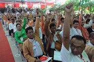 Delegates of the National League for Democracy gesture to vote during their first ever party conference at the Royal Rose Hall in Yangon on March 9, 2013. Aung San Suu Kyi's opposition wraps up its historic first congress Sunday, finalising its leadership line-up as it faces infighting that has overshadowed the launch of its bid to rule Myanmar after 2015 polls