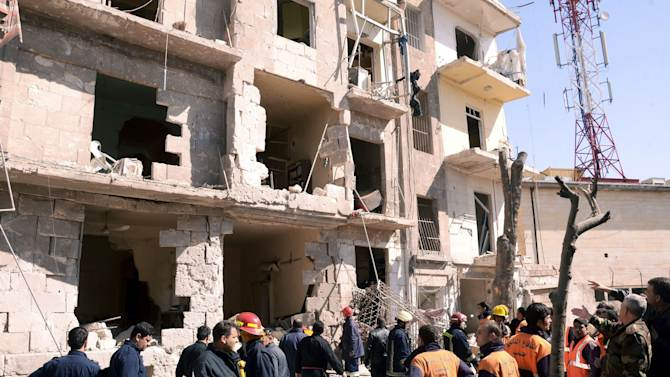 """This photo provided by the Syrian official news agency SANA shows Syrian rescue teams investigating the scene after an explosion in a residential neighborhood in Aleppo, Syria, Sunday, March 18, 2012. The state news agency said the explosion was a """"terrorist bombing."""" The report by SANA gave no information on casualties in what appeared to be the second attack in two days on cities where President Bashar Assad's regime enjoys strong support. (AP Photo/SANA)"""