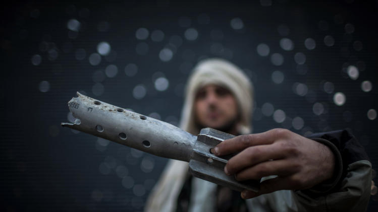 FILE - A Free Syrian Army fighter displays a damaged ordinance in Aleppo, Syria, Tuesday, Jan. 15, 2013. (AP Photo/Andoni Lubaki, File)