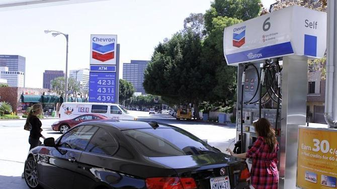 A woman stands at a gas pump at a Chevron gasoline station in Los Angeles