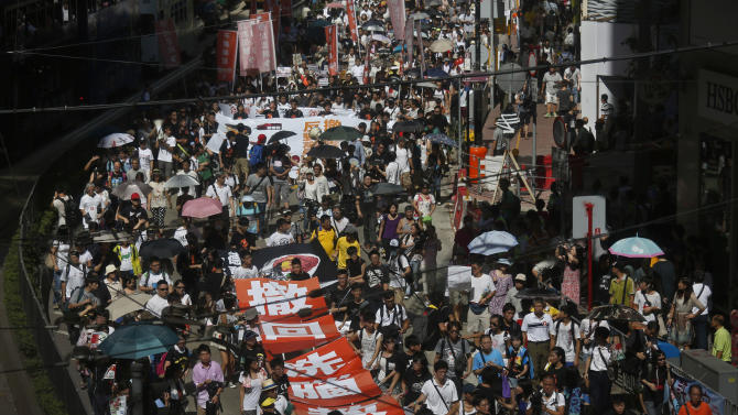 Thousands of people march on a downtown street in Hong Kong Sunday, July 29, 2012 to protest the upcoming introduction in schools of Chinese patriotism classes that they fear will lead to brainwashing. Teachers, parents, students and pro-democracy activists marched Sunday to the government headquarters of the semiautonomous territory to protest against the new curriculum, which authorities are encouraging schools to begin using when classes resume in September. (AP Photo/Vincent Yu)