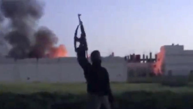 In this Thursday March 28, 2013 image taken from video obtained from the Ugarit News, which has been authenticated based on its contents and other AP reporting, shows a building at the  Syrian government checkpoint on fire, in Dael less than 15 kilometers (10 miles) from the Jordanian border in Daraa province, Syria. Thursday, March 28, 2013. Syrian rebels on Friday captured a strategic town near the border with Jordan after a day of fierce clashes that killed dozens of people, activists said, as opposition fighters expand their presence in the south, considered a gateway to Damascus.  (AP Photo/Ugarit News via AP video)