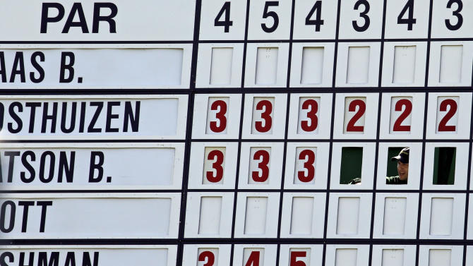 A course worker changes the scores on the seventh fairway leader board during the second round of the Masters golf tournament Friday, April 11, 2014, in Augusta, Ga. (AP Photo/David J. Phillip)