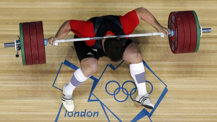 Matthias Steiner of Germany gets hit by the weights while failing to make a successful lift  in the men's over 105-kg, group A, weightlifting competition at the 2012 Summer Olympics, Tuesday, Aug. 7, 2012, in London. (AP Photo/Ng Han Guan)
