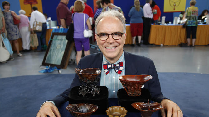 """In this Saturday, July 23, 2011 photo, Asian art expert and veteran """"Antiques Roadshow."""" appraiser Lark Mason poses with a collection of Chinese rhinoceros horned cups  in Tulsa, Okla. PBS says the collection was judged by Mason to be worth $1 million to $1.5 million, the most valuable item brought in for appraisal in the history of """"Antiques Roadshow,"""" which will air its 16th season next year. (AP Photo/WGBH)"""
