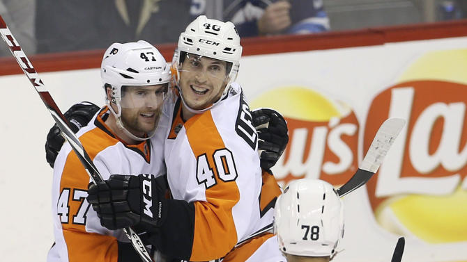 Philadelphia Flyers' Andrew MacDonald (47), Vincent Lecavalier (40), and Pierre-Edouard Bellemare (78) celebrate after Lecavalier scored during the third period of an NHL hockey game in Winnipeg, Sunday, Dec. 21, 2014. (AP Photo/The Canadian Press, Trevor Hagan)
