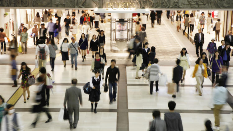 """People walk through a concourse at the Yokohama Station in Yokohama near Tokyo Friday, May 10, 2013. The dollar soared above 100 yen for the first time in more than four years Friday, driven by improved U.S. economic figures and  Tokyo's aggressive credit-easing that aims to revive Japan's sluggish economy. The weaker yen is a boon to Japan's major auto and electronics exporters. The government said the yen's fall signaled that Prime Minister Shinzo Abe's policy mix of increased public spending and aggressive monetary easing, dubbed """"Abenomics,"""" was proving successful. (AP Photo/Koji Sasahara)"""