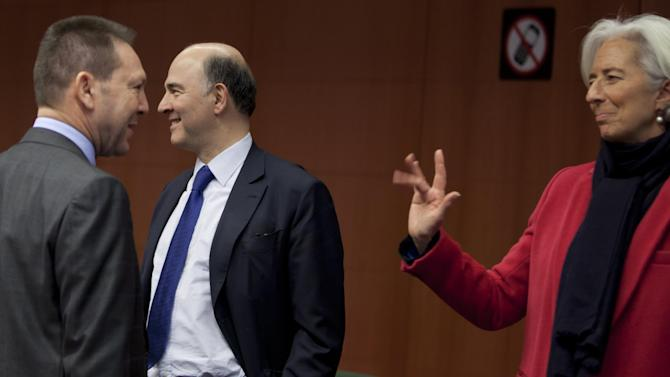Managing Director of the International Monetary Fund Christine Lagarde, right, waves to Greek Finance Minister Yannis Stournaras, left, and French Finance Minister Pierre Moscovici during a meeting of  eurogroup finance ministers in Brussels on Monday, March 4, 2013. The eurogroup finance ministers are set to discuss details of a bailout for cash-strapped Cyprus, further steps of assistance for Portugal and Ireland as well as the controversial issue of direct banking recapitalizations through Europe's permanent rescue fund. (AP Photo/Virginia Mayo)