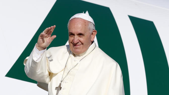 Pope Francis waves to reporters as he boards a plane to Amman, Jordan, for a three-day trip to the Middle East including the West Bank and Israel, at Rome's Fiumicino international airport, Saturday, May 24, 2014. On the first leg of his trip, Pope Francis will get a firsthand look at the plight of Syrian refugees and witness the toll the civil war next door is taking on Jordan. (AP Photo/Riccardo De Luca)