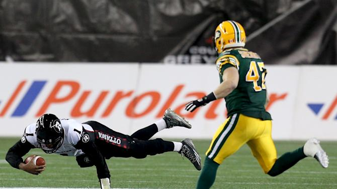 Ottawa Redblacks quarterback Burris falls after eluding a sack with Edmonton Eskimos' Sherritt in pursuit during the CFL's 103rd Grey Cup championship football game in Winnipeg