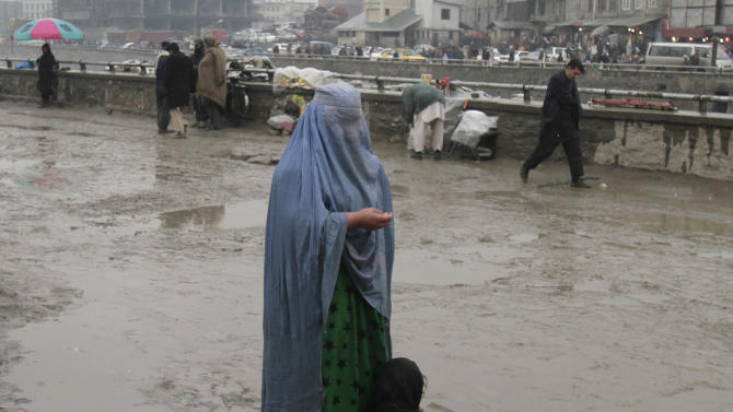 An Afghan woman begs with her child on a rainy day in Kabul, Afghanistan. (AP Photo/Ahmad Jamshid)