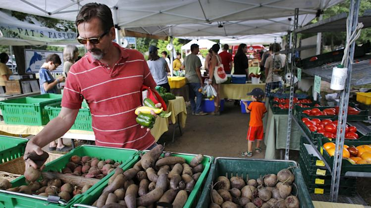"""In this July 30, 2014 photo, David Mann, of Pawtucket, R.I., shops for vegetables at the Wishing Stone Farm stand at a farmers market, in Providence, R.I. Across New England, the number of farms has grown by 5 percent since 2007, contrary to the national trend. Farmers and industry experts say the popularity of the """"buy local"""" food movement here has helped create a market for new, small farms. (AP Photo/Steven Senne)"""