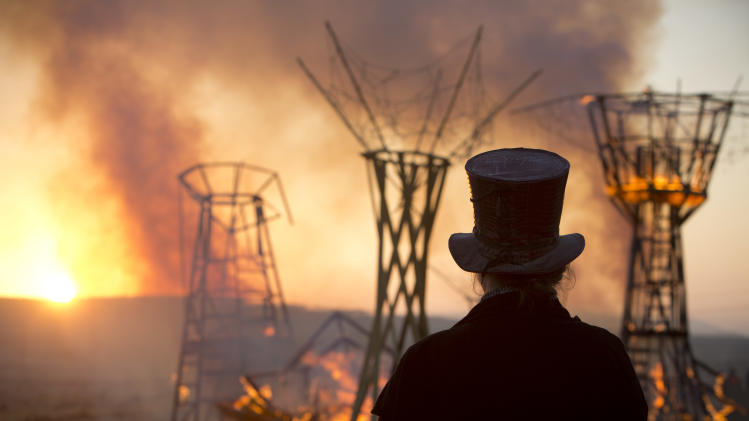 In this Saturday, June 7, 2014, photo, a man looks at a wooden sculpture that was set on fire during Israel's first Midburn Festival, modeled after the popular Burning Man Festival held annually in Nevada's Black Rock Desert, near the Israeli kibbutz of Sde Boker. Some 3,000 people set up a colorful encampment in the dusty moonscape, swinging from hoops by day and burning giant wooden sculptures by night. (AP Photo/Oded Balilty)