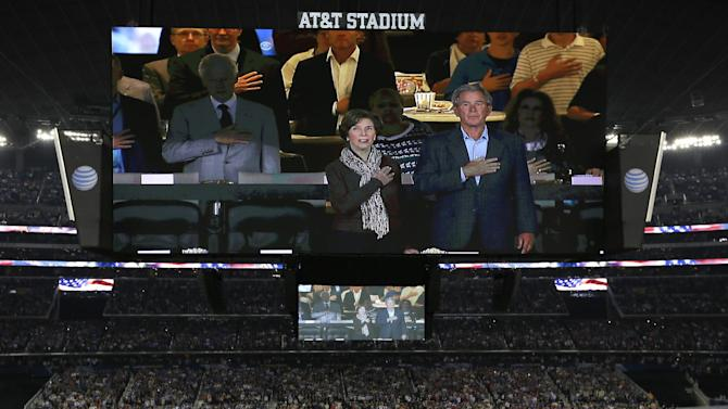 Former president George W. Bush and wife Laura are seen with former president Bill Clinton, left, on the overhead scoreboard during the national anthem before the NCAA Final Four tournament college basketball championship game between Connecticut and Kentucky, Monday, April 7, 2014, in Arlington, Texas. (AP Photo/Tony Gutierrez)