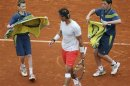 Ball boys bring towels to Nadal of Spain during his men's singles match against Klizan of Slovakia at the French Open tennis tournament in Paris