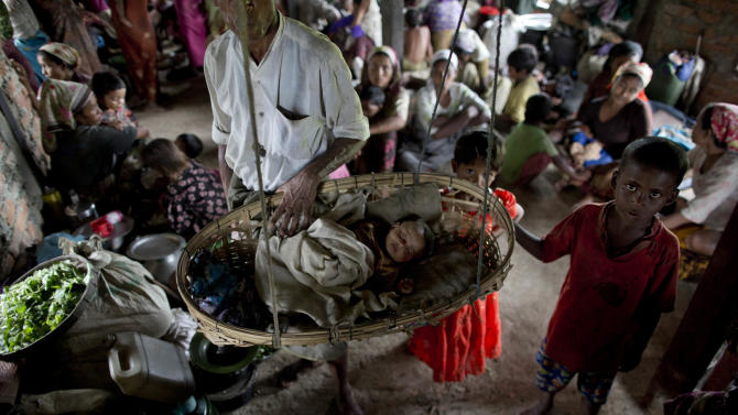 In this May 15, 2013 photo, displaced Rohingya people take shelter in a building adjoining a mosque, outskirts of Sittwe, western Rakhine State, Myanmar. Many of those displaced by recent violence live under apartheid-like conditions in tattered canvas tents, and long bamboo houses shared by dozens of families.(AP Photo/Gemunu Amarasinghe)