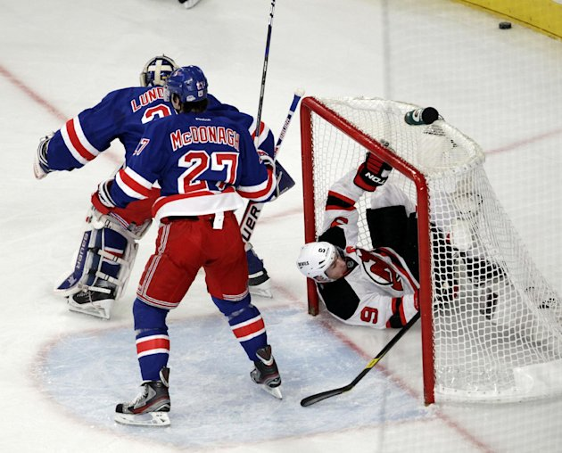 New Jersey Devils' Zach Parise, right, goes into the net after his shot was deflected by New York Rangers goalie Henrik Lundqvist, rear, of Sweden, and Ryan McDonagh (27) during the first period of Ga