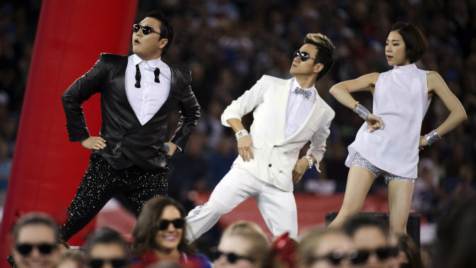 """FILE - In this Sunday, Dec. 16, 2012 file photo, South Korean entertainer PSY, left, performs the song """"Gangnam Style"""" during halftime of an NFL football game between the Buffalo Bills and Seattle Seahawks, in Toronto. Viral star PSY has reached a new milestone on YouTube. The South Korean rapper's video for """"Gangnam Style"""" has reached 1 billion views, the first time any clip has surpassed that mark on the streaming service. PSY passed 1 billion Friday, Dec. 21, 2012, and was already approaching 400,000 more views by mid-morning. (AP Photo/The Canadian Press, Nathan Denette, File)"""