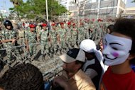 Protesters confront soldiers during a demonstration against the interim military leadership in the Abbassiya district of Cairo on Sunday. Egypt&#39;s ruling military has promised that the forthcoming presidential election will be free and has pledged to hand power to the winner by the end of June