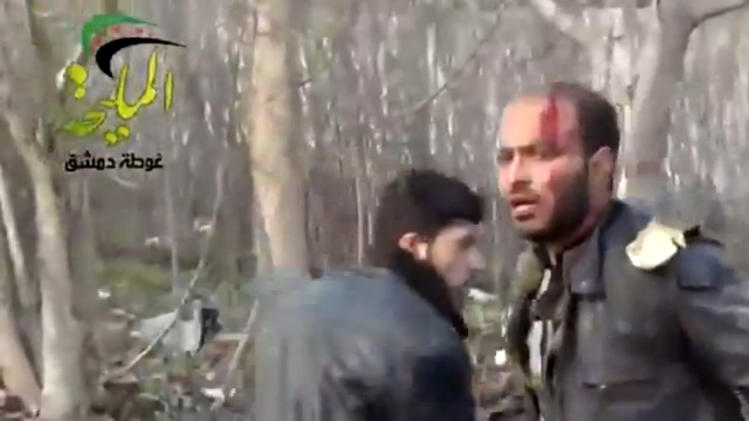 This citizen journalism image taken from video provided by Shaam News Network, which has been authenticated based on its contents and other AP reporting, shows a wounded man at the site of a Syrian government airstrike on a gas station in the eastern Damascus suburb of Mleiha, Syria, Wednesday, Jan. 2, 2013. Activists say dozens of people have been killed or wounded in an air raid on a gas station near the capital Damascus. (AP Photo/Shaam News Network via AP video)
