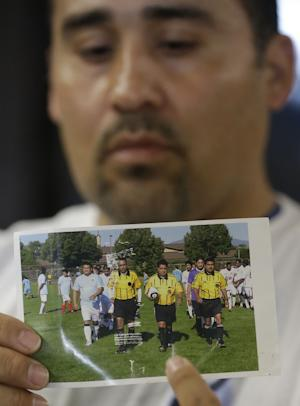 Jose Lopez, points to a undated photo of Riccardo Portillo, center, his brother-in-law, following a news conference Thursday, May 2, 2013, at Intermountain Medical Center, in Murray, Utah. A longtime Utah soccer referee is in a coma after being punched by a teenage player unhappy with one of his calls during a weekend game, and his family says they're hoping for the man's miraculous recovery and want justice for him. Ricardo Portillo, 46, has swelling in his brain and his recovery is uncertain as he remains in critical condition, Dr. Shawn Smith said Thursday at the Intermountain Medical Center in the Salt Lake City suburb of Murray. Police say a 17-year-old player in a recreational soccer league punched Portillo after the man called a foul on him and issued him a yellow card. The teen has been booked into juvenile detention on suspicion of aggravated assault. Those charges could be amplified if Portillo dies. (AP Photo/Rick Bowmer)