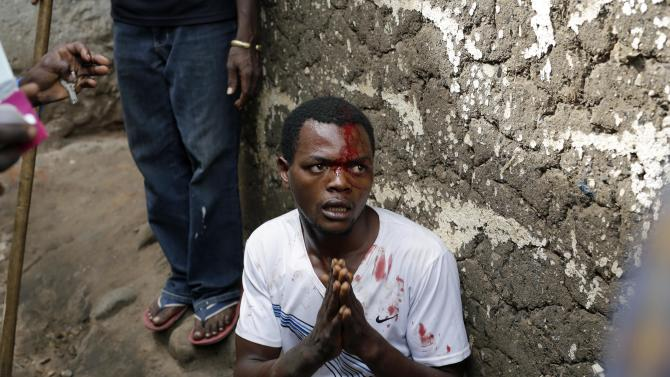 Jean Claude Niyonzima, a suspected member of the ruling party's Imbonerakure youth militia, pleads for his life as he is surrounded at his house by demonstrators protesting President Pierre Nkurunziza's decision to seek a third term in office in the Cibitoke district of Bujumbura, Burundi, Thursday May 7, 2015. At least one protestor has died in clashed with the widely feared Imbonerakure militias and police, sending scores to the streets seeking revenge. This suspect eventually managed to flee under a hail of stones into a covered sewer, where he remained till the army fired shots into the air to disperse the crowd.(AP Photo/Jerome Delay)