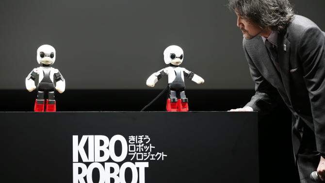 """Humanoid communication robot Kirobo, center, talks with Fuminori Kataoka, project general manager from Toyota Motor Corp., during a press unveiling in Tokyo Wednesday, June 26, 2013. The world's first space conversation experiment between a robot and humans is ready to be launched. Developers from the Kirobo project, named after """"kibo"""" or hope in Japanese and """"robot,"""" gathered to demonstrate the humanoid robot's ability to talk. Kirobo, jointly developed by advertising and PR company Dentsu Inc., Research Center for Advanced Science and Technology, the University of Tokyo, Robo Garage Co. and Toyota., is scheduled to be launched from the Tanegashima Space Center on Aug. 4, 2013. (AP Photo/Shizuo Kambayashi)"""