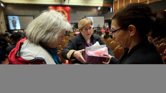 Shira Stern, center, of Marlboro, N.J., a chaplain for Disaster and Spiritual Care with the Amercian Red Cross, collects boxes of tissues to distribute among the attendees of Lu Lingzi's memorial service at Metcalf Hall in Boston University's George Sherman Student Union on Monday, April 22, 2013. At left is Carole Beauchamp, of Grand Blanc, Mich., a disaster mental health volunteer with the American Red Cross. At right is Lucy Torres, of Stoneham, Mass., the executive secretary for Boston University's Dean of Students, Kenneth Elmore. Lingzi was killed in the Boston Marathon bombings. (AP Photo/Boston Globe, Dina Rudick, Pool)