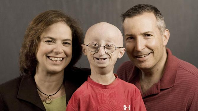 """This undated photo provided by HBO shows Sam Berns, the subject of the HBO documentary, """"Life According to Sam,"""" center, with his parents, Leslie Gordon, left, and Scott Berns. Sam Berns, 17, died Friday, Jan. 10, 2014 of complications from Hutchinson-Gilford progeria syndrome, commonly known as progeria. Hundreds of people, including New England Patriots owner Robert Kraft, attended his funeral on Tuesday, Jan. 14, 2014. (AP Photo/HBO, Sean Fine)"""