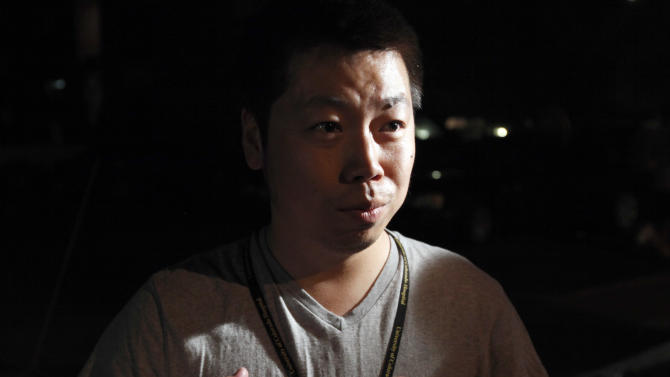 """Dr. Yi Zhang speaks about living a floor below the apartment of alleged gunman James Holmes Friday, July 20, 2012 in Aurora , Colo. Authorities reported that 12 died and more than three dozen people were shot during an assault at a movie theatre midnight premiere of """"The Dark Knight Rises."""" (AP Photo/Alex Brandon)"""