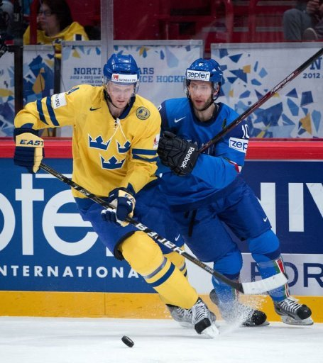 Sweden's Staffan Kronwall (L) fights for the puck with Italy's Giulio Scandella