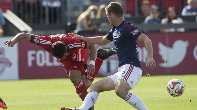 Toronto FC's Gilberto, left, back-heels the ball past Chivas USA's Eriq Zavaleta during the second half of an MLS soccer game in Toronto on Sunday, Sept. 21, 2014. (AP Photo/The Canadian Press, Chris Young)