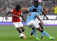 Gervinho (L) of Arsenal tries to get pass Vincent Kompany of Manchester City during a friendly match in Beijing. Manchester City beat Arsenal 2-0