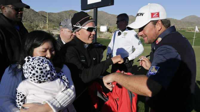 Graeme McDowell, of Northern Ireland, signs autographs for fans after defeating Alexander Noren 1 up in 20 holes in the second round of the Match Play Championship golf tournament, Friday, Feb. 22, 2013, in Marana, Ariz. (AP Photo/Ted S. Warren)