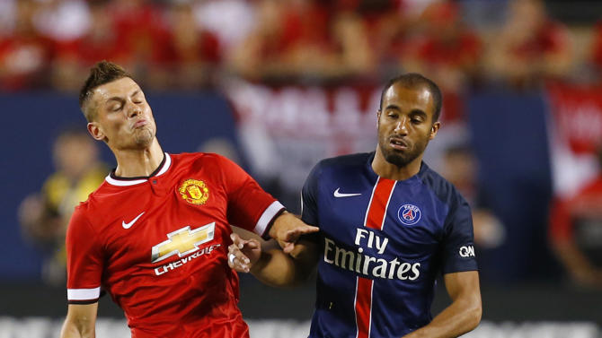 Manchester United's Morgan Schneiderlin (L) in action with Paris St Germain's Lucas Moura