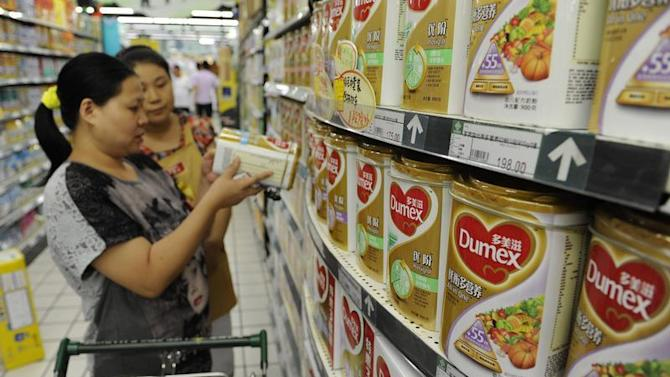 A sales assistant helps a customer to select Dumex milk powders at a supermarket in Hefei