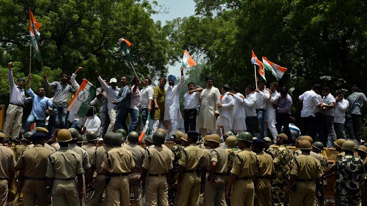 Indian Congress Party supporters stand on a police barricade during a protest against price rises as India's parliament opens ahead of the Budget session in New Delhi on July 7, 2014