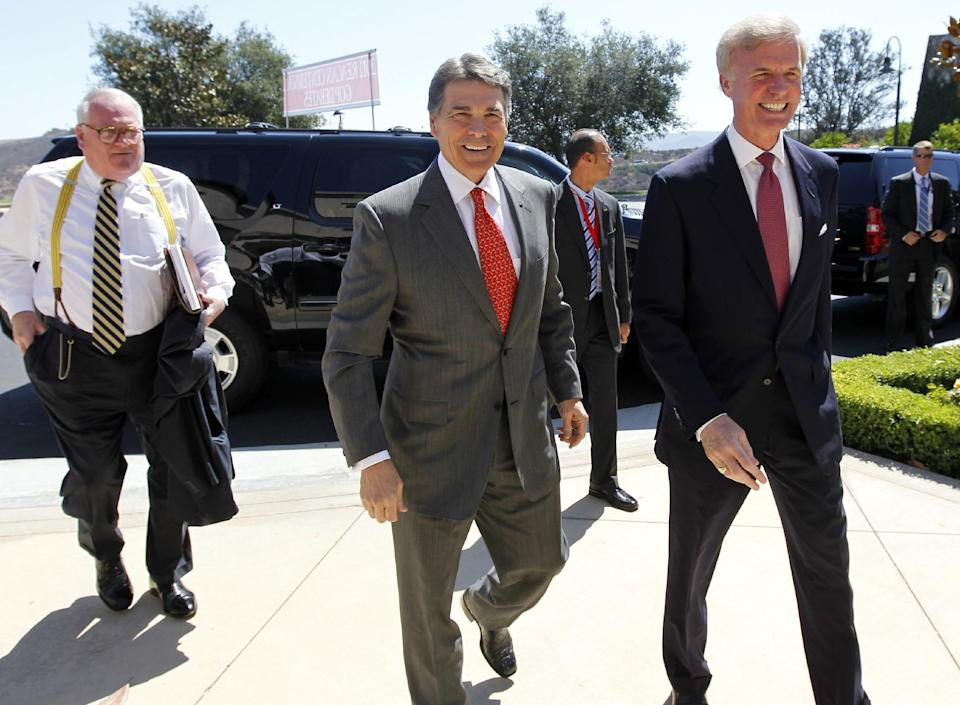 Republican presidential candidate Texas Gov. Rick Perry, center, is met by Frederick J. Ryan, Jr., chairman of the Ronald Reagan President Foundation, as he arrives for a Republican presidential debate at the Reagan Library Wednesday, Sept. 7, 2011, in Simi Valley, Calif. (AP Photo/Chris Carlson, Pool)