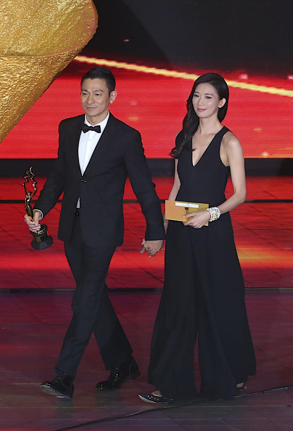 Hong Kong actor Andy Lau, left, walks with Taiwanese model Lin Chi-ling at the award ceremony for the Beijing Film Festival in Beijing Tuesday April 23, 2013.(AP Photo) CHINA OUT