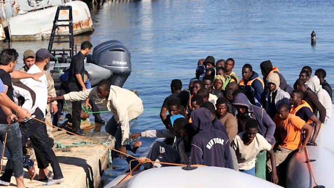 Libyan coastguards tie up a boat carrying rescued migrants at a naval base near Tripoli on September 29, 2015