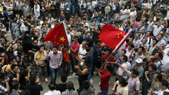 Several anti-Occupy protesters are surrounded by pro-democracy protesters at Mongkok shopping district in Hong Kong