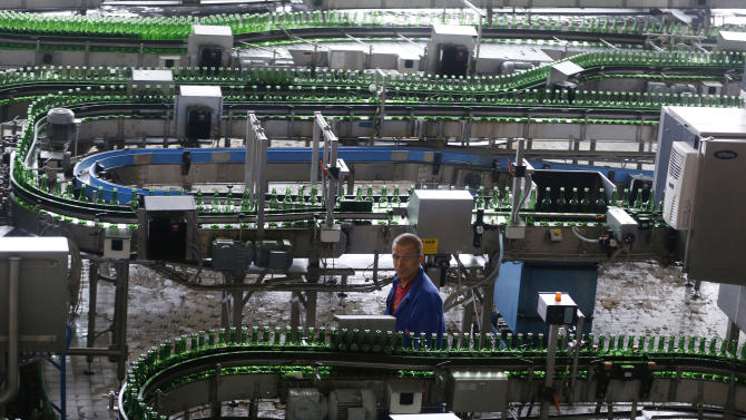 In this Tuesday, Oct. 30, 2012 photo a worker walks past a line of beers at the Budejovicky Budvar brewery  in Ceske Budejovice, Czech Republic. They've been arguing about a name for 106 years. A small brewer in the Czech Republic and the world's biggest beer maker have been suing each other over the right to put the word Budweiser on their bottles in what has become a David versus Goliath corporate saga. A deal, it seems, will have to wait a bit longer because settlement talks between state-owned Budejovicky Budvar and Anheuser-Busch, a U.S. company now part of AB InBev, have collapsed, according to Budvar's director general, Jiri Bocek. (AP Photo / Petr David Josek)
