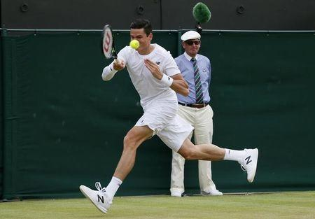 Milos Raonic of Canada hits a shot during his match against Nick Kyrgios of Australia at the Wimbledon Tennis Championships in London
