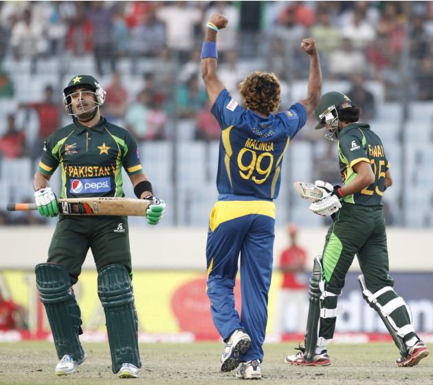 Pakistan's Akmal leaves the field as Sri Lanka's Malinga celebrates his dismissal during their 2014 Asia Cup final match in Dhaka