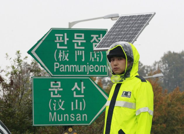 A police officer stands guard to block North Korean defector's planned rally on a road in Paju near demilitarized zone, South Korea, Monday, Oct. 22, 2012. South Korea has banned activists from launch