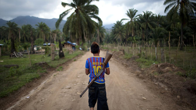 In this May 5, 2012 photo, Enrique Martinez, 17, with a rifle slung over his back, patrols an area of La Confianza, Honduras, a city developed from land seized by small-scale farmers from one of Honduras' richest men. The collection of tin-and-wood shacks boasts a health center, a school, a meeting hall, and a store. The land seizure has spawned a violent land conflict between the farmers and owner, billionaire Miguel Facusse, that has killed at least 63 people, mostly peasants, in the last three years in the Bajo Aguan Valley. (AP Photo/Rodrigo Abd)