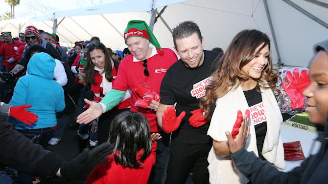 """IMAGE DISTRIBUTED FOR MATTEL - From right, WWE stars Diva Eve and The Miz, Bryan Stockton, Mattel CEO, and Deidre Lind, Executive Director, Mattel Children's Foundation, greet Los Angeles school children at Mattel's Southern California headquarters for a """"Winter Wonderland"""" featuring 220 tons of snow on Thurs., Dec. 13, 2012 in El Segundo, Calif. (Photo by Casey Rodgers/Invision for Mattel/AP Images)"""