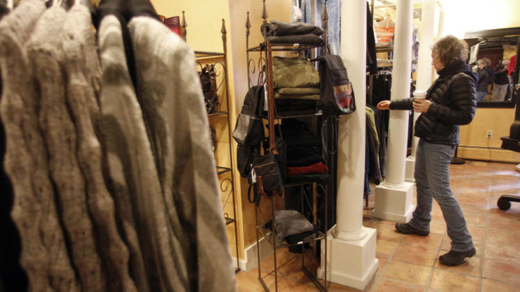 In this Feb. 28, 2012 photo, Laurie Hanson looks over clothing at the Adorn clothing store in Montpelier, Vt. Consumers earned a little more in January and spent most of the extra money. The gains should keep the economy growing at a modest pace. (AP Photo/Toby Talbot)